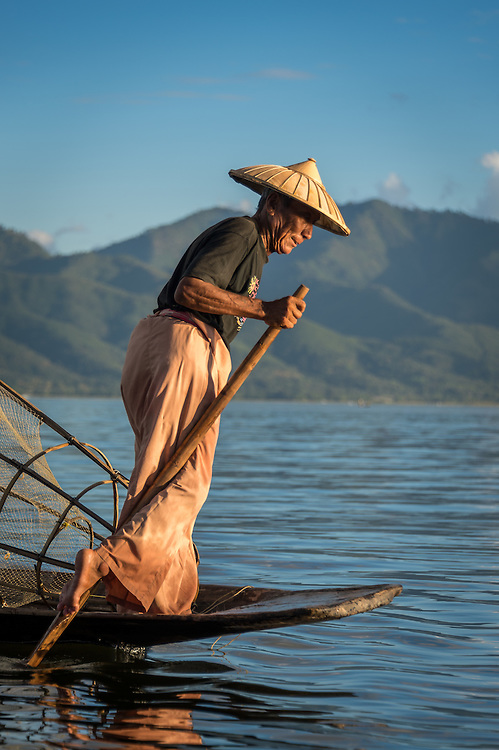 INLE LAKE, MYANMAR - CIRCA DECEMBER 2013: Fisherman rowing a typical boat in the Inle Lake, Myanmar