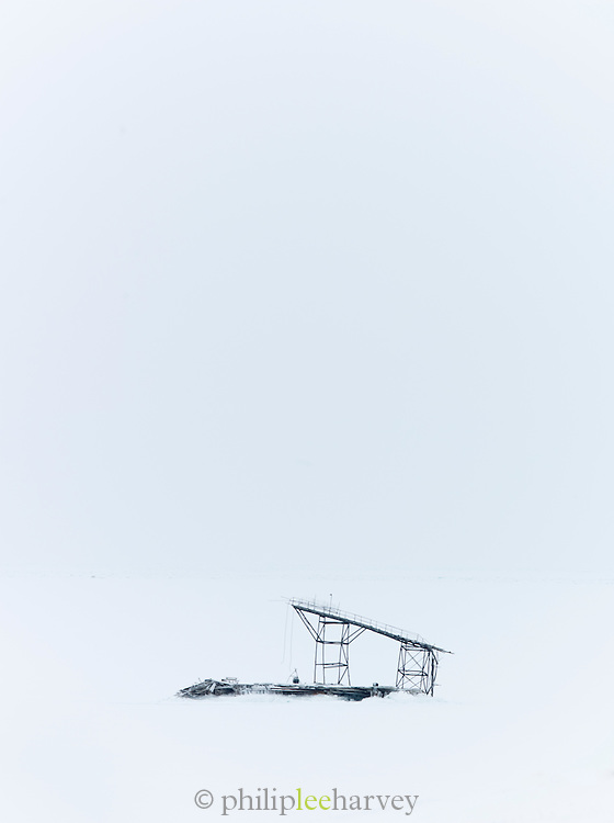 An old abandoned mining factory, buried in snow in the frozen landscape in Spitsbergen. Spitsbergen is the largest island of the arctic archipelago Svalbard, of Norway