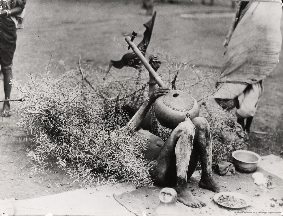 Fakir in thorn bush with musical instrument, Benares, India, 1929