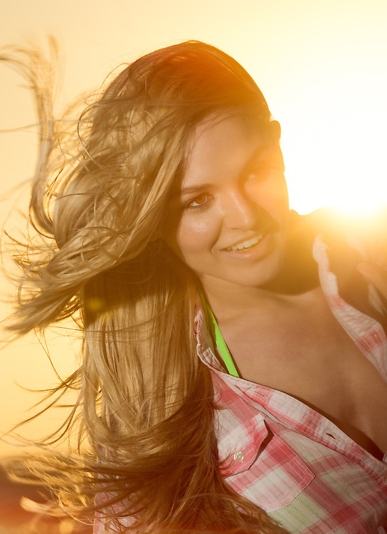 Young woman happy in the afternoon in the beach, smiling with sun flare in the back.