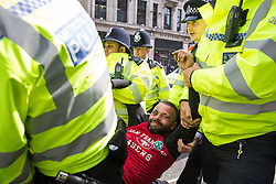 London, UK. 18th April 2019. Police officers move in to arrest a climate change campaigner from Extinction Rebellion as part of a large police operation to try to clear Oxford Circus of protesters on the fourth day of International Rebellion activities to call on the British government to take urgent action to combat climate change.