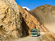 A Denali National Park Green Shuttle Bus drives the Park Road through yellow mountains near Polychrome Overlook, Alaska, USA. Since 1972, traffic on the 92-mile-long Denali Park Road has been limited mostly to buses, thereby protecting wildlife, air quality, and wilderness aesthetics.