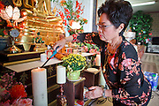 24 OCTOBER 2010 - CHANDLER, AZ: A woman lights candles during prayers during the Ok Phansa services to mark the end of Buddhist Lent at Wat Pa, in Chandler, AZ, Sunday October 24. Buddhist Lent is a time devoted to study and meditation. Buddhist monks remain within the temple grounds and do not venture out for a period of three months starting from the first day of the waning moon of the eighth lunar month (in July) to the fifteenth day of the waxing moon of the eleventh lunar month (in October). Ok Phansa Day marks the end of the Buddhist lent and falls on the full moon of the eleventh lunar month, this year Oct 23. Wat Pa, a Thai Theravada Buddhist temple, celebrated Ok Phansa Day on October 24.    Photo by Jack Kurtz