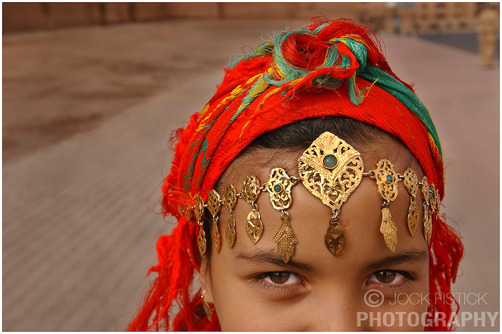 A young girl wears traditional Moroccan clothes and jewelry outside the Kasbah de Taourirt, built in the 17th century, in Ouarzazate, Morocco. (Photo © Jock Fistick)