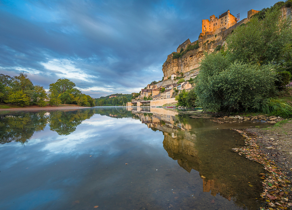 The Château de Beynac is a castle situated in the commune of Beynac-et-Cazenac, in the Dordogne département of France. The castle is one of the best-preserved and best known in the region.<br /> <br /> This Middle Ages construction, with its austere appearance, is perched on top of a limestone cliff, dominating the town and the north bank of the Dordogne River. The castle was built in the 12th century by the barons of Beynac (one of the four baronies of Périgord) to close the valley. The sheer cliff face being sufficient to discourage any assault from that side, the defences were built up on the plateau: double crenellated walls, double moats, one of which was a deepened natural ravine, double barbican.<br /> <br /> The oldest part of the castle is a large, square-shaped, Romanesque keep with vertical sides and few openings, held together with attached watch towers and equipped with a narrow spiral staircase terminating on a crenellated terrace. To one side, a residence of the same period is attached; it was remodelled and enlarged in the 16th and 17th centuries. On the other side is a partly 14th century residence side-by-side with a courtyard and a square plan staircase serving the 17th century apartments. The apartments have kept their woodwork and a painted ceiling from the 17th century. The Salle des États (States' Hall) has a Renaissance sculptured fireplace and leads into a small oratory entirely covered with 15th century frescoes, included a Pietà, a Saint Christopher, and a Last Supper in which Saint Martial (first bishop of Limoges) is the maître d'hôtel.<br /> <br /> At the time of the Hundred Years' War, the fortress at Beynac was in French hands. The Dordogne was the border between France and England. Not far away, on the opposite bank of the river, the Château de Castelnaud was held by the English. The Dordogne region was the theatre of numerous struggles for influence, rivalries and occasionally battles between the English and French supporters. Howev