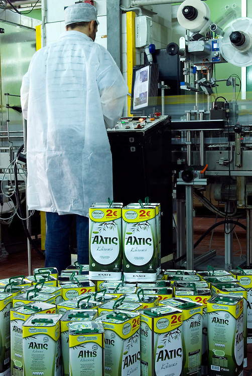 worker operates the olive oil tin filling machine