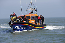 © Licensed to London News Pictures. 09/10/2021. Dungeness, UK. An RNLI lifeboat carries migrants ashore at Dungeness in Kent after crossing the English Channel. Hundreds of migrants have made the crossing in the calm weather this week. Photo credit: Sean Aidan/LNP
