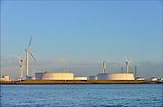Nederland, Rotterdam, 3-3-2015Windmolens in de Rijnmond, Rotterdamse haven. Hier bij opslagtanks van oude energie, aardolie, olie, in de nieuwste petroleumhaven op de Maasvlakte.FOTO: FLIP FRANSSEN/ HOLLANDSE HOOGTE