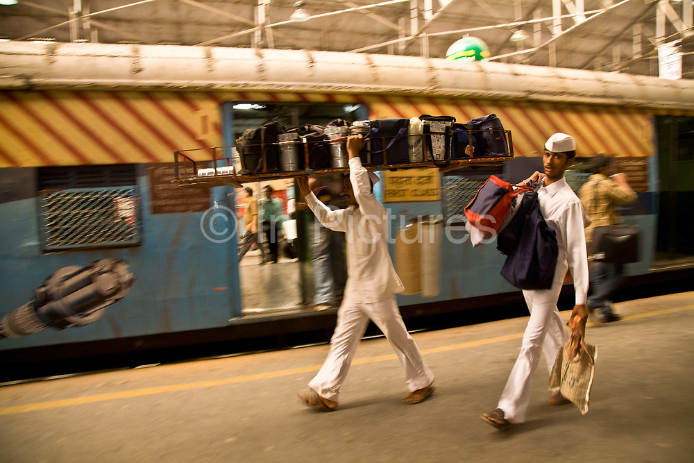 Dabbawallahs (tiffinwallah) travel across Mumbai's using its extensive rail network as well as using their own bicycles delivering freshly prepared home cooked food to office workers throughout the city. This 125 year tradition, unique to the city employs 5000 tiffinwallahs delivering an average of 200.000 meals a day which are kept in the tin dabbas which are delivered by using both bicycle and the city's rail network. The dabbawallahs are distinctive by their impeccable white uniform which includes a Gandhi style cap and a service second to none which is the toast and the praise of enterprises such as Forbes magazine and other blue chip companies in terms of service, punctuality and delivery, Mumbai (Bombay), India