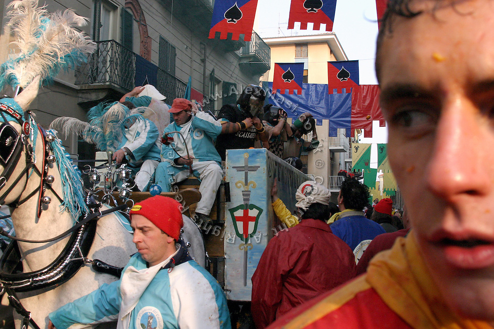 A members of the Mercenaries is waiting for the horse-van behind him to enter the City Square and start to fight again during The Battle of the Oranges in Ivrea, pop. 30.000. During the days of the Carnival, the town becomes crammed with tourists coming to witness the event which finds its roots at the end of the XII Century, when the people led an insurrection against the local tyrant, Count Ranieri of Biandrate, who was exercising the 'jus primae noctis' rule (having the first night) on the local young brides. The battle to overthrow him is represented with a 3-day-fight between factions in which more then 400 tonnes of oranges are thrown. During the celebrations, food stalls, bands playing music, and parades are also present, giving it a typical Medieval atmosphere. .