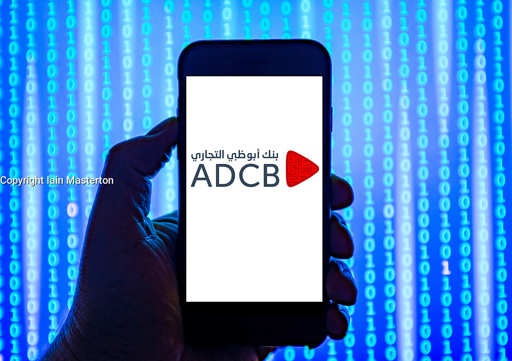 Person holding smart phone with ADCB bank logo displayed on the screen. EDITORIAL USE ONLY