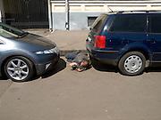 Obdachloser Mann schläft auf einem Parkplatz zwischen Autos auf der gegenüberliegenden Straßenseite des Kasaner Bahnhofs (Kasanski woksal) welcher einer der neun Bahnhöfe in Moskau ist. Er liegt am Komsomolskaja-Platz, in unmittelbarer Nähe zum Jaroslawler und dem Leningrader Bahnhof, und ist bis heute einer der größten Bahnhöfe der russischen Hauptstadt. <br /> <br /> Homeless person is sleeping on a parking place in between cars on the opposite site of the Kazansky Rail Terminal (Kazansky vokzal) which is one of eight rail terminals in Moscow, situated on the Komsomolskaya Square, across the square from the Leningradsky and Yaroslavsky terminals.