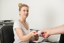 Patient giving a health insurance card to receptionist, Munich, Bavaria, Germany