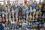 Stall in the indoor antique market in Yu Yuan Garden, downtown Shanghai. The pots and ceramics being sold by this family business on the top floor of the market are not genuine antiques. Many are fakes, which are sold to the more gullible tourists. Genuine antiques can be bought but the prices reflect their age considerably.