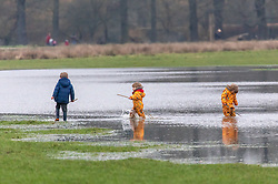 © Licensed to London News Pictures. 31/01/2021. London, UK. Kids play in flooded fields in Richmond Park, South West London this afternoon as the Met Office issue further weather warnings for snow, rain and flooding for large parts of the UK. The Met office has issued weather warnings for much of the UK this weekend for snow, torrential rain and flooding with disruption to travel as the stormy weather continues. Photo credit: Alex Lentati/LNP