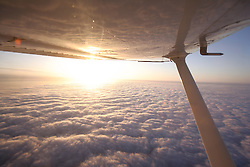 Cessna 172 flying over an undercast