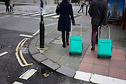 A couple of tourists walk through London's Bloomsbury carrying matching green cases.