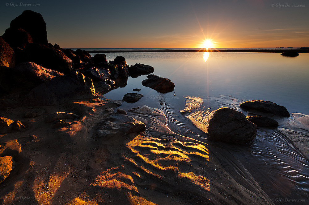 The sun sets over the Irish Sea and a large pool which had formed on the main beach at Porth Tyn Tywyn near Rhosneigr, Anglesey, Wales