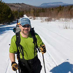 A man cross-country skiing on a backcountry trail near Greenville, Maine. The Shaw Trail between Medawisla Wilderness Camps and West Branch Pond Camps. Big Spencer Mountain is in the distance.