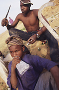 Badawa Ghetto Street Gang on the outskirts of Kano. They are Muslim but drink alcohol, smoke and inject hard drugs..The implementation of Islamic Sharia Law across the twelve northern states of Nigeria, centres upon Kano, the largest Muslim Husa city, under the feudal, political and economic rule of the Emir of Kano. Islamic Sharia Law is enforced by official state apparatus including military and police, Islamic schools and education, plus various volunteer Militia groups supported financially and politically by the Emir and other business and political bodies. Fanatical Islamic Sharia religious traditions  are enforced by the Hispah Sharia police. Deliquancy is controlled by the Vigilantes volunteer Militia. Activities such as Animist Pagan Voodoo ceremonies, playing music, drinking and gambling, normally outlawed under Sharia law exist as many parts of the rural and urban areas are controlled by local Mafia, ghetto gangs and rural hunters. The fight for control is never ending between the Emir, government forces, the Mafia and independent militias and gangs. This is fueled by rising petrol costs, and that 70% of the population live below the poverty line. Kano, Kano State, Northern Nigeria, Africa