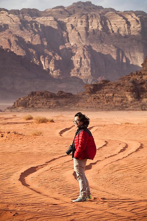 SeongRyeong Bak walks down a Jeep track through the red sand desert of Wadi Rum, Jordan