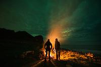 Standing around an campfire with northern lights - aurora borealis in the sky overhead, Unstad, Vestvågøy, Lofoten Islands, Norwya