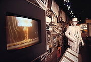 At Los Alamos, New Mexico, on the grounds of the Los Alamos National Lab, the Bradbury Science Center puts a positive spin on the development of nuclear weapons with historical displays. Here a plaster Robert Oppenheimer is frozen in time watching an endless-loop video of the mushroom clouds of atomic bomb tests. Other exhibits have sanitized versions of nuclear weapons casings and hand-on nuclear weapons design stations. Los Alamos, New Mexico.