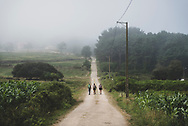 Three people walk the Camino between the coastal towns of Muxia and Finisterre in Spain. (July 23, 2018)<br />