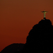The iconic Cristo Redentor, Christ the Redeemer statue at sunset atop the mountain Corcovado shot from Sugar Loaf Mountain. The Christ statue was voted one of the seven wonders of the modern world in 2007. It was designed by Brazilian Heitor de Silva Costa and was inaugurated in 1931 having taken years to assemble. Rio de Janeiro, Brazil. 24th August 2010. Photo Tim Clayton...