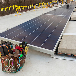 Tools and a solar panel on the roof of a commercial building in Greenfield, Massachusetts.