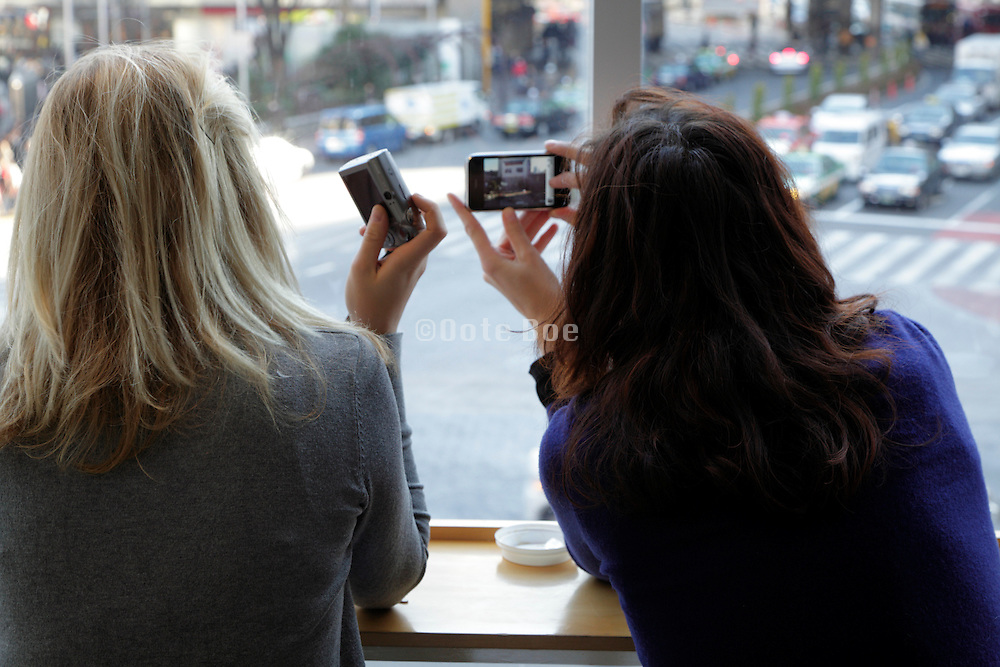girl friends taking pictures one with an Apple Iphone other with a traditional digital camera