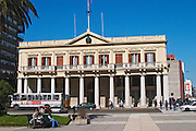 On the Plaza Independencia Independence Square. . The front of a government building Palacio Estavez Palace with a colonnade and a white local bus on the street. Pedestrians. People sitting on a park bench. Montevideo, Uruguay, South America