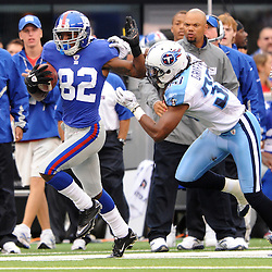 Wide receiver Mario Manningham #82 of the New York Giants runs through a tackle during second half NFL football action between the New York Giants and Tennessee Titans at New Meadowlands Stadium in East Rutherford, New Jersey. The Titans defeated the Giants .