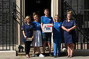 Matthew Tovey c and other NHS workers from the grassroots NHSPay15 campaign pose outside 10 Downing Street before presenting a petition signed by over 800,000 people calling for a 15% pay rise for NHS workers on 20th July 2021 in London, United Kingdom. At the time of presentation of the petition, the government was believed to be preparing to offer NHS workers a 3% pay rise in recognition of the unique impact of the pandemic on the NHS.