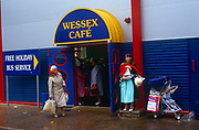 Holidaymakers shelter from typical English summer rain during their stay at the regenerated Butlins holiday centre at Minehead. Outside a large sign saying Wessex Cafe, a reference to our Saxon past, a mother struggles to hold a wriggling child while an older woman holds her holiday bag on the wet pavement. Butlins is an institution for the British working classes who after the war had the opportunity to spend their summers at special resorts in seaside towns that provided entertainment and fun. Butlins and other camp businesses went into decline when the masses preferred Spanish vacations but have since been revived as travel costs have again soared and holidays at home are once again popular.