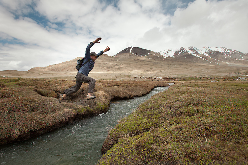 Writer Mike Finkel jumps over a river. The Kyrgyz settlement of Tchelab, near Chaqmaqtin lake, Haji Bootoo Boi's camp...Trekking through the high altitude plateau of the Little Pamir mountains (average 4200 meters) , where the Afghan Kyrgyz community live all year, on the borders of China, Tajikistan and Pakistan.