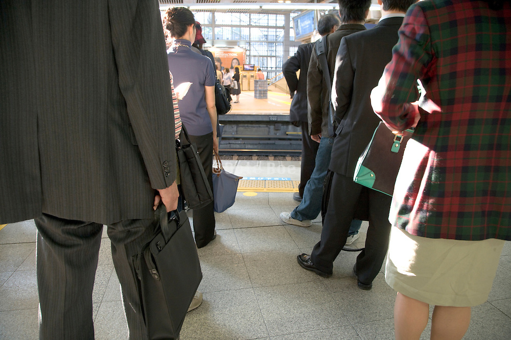 commuters waiting in line for the train to arrive