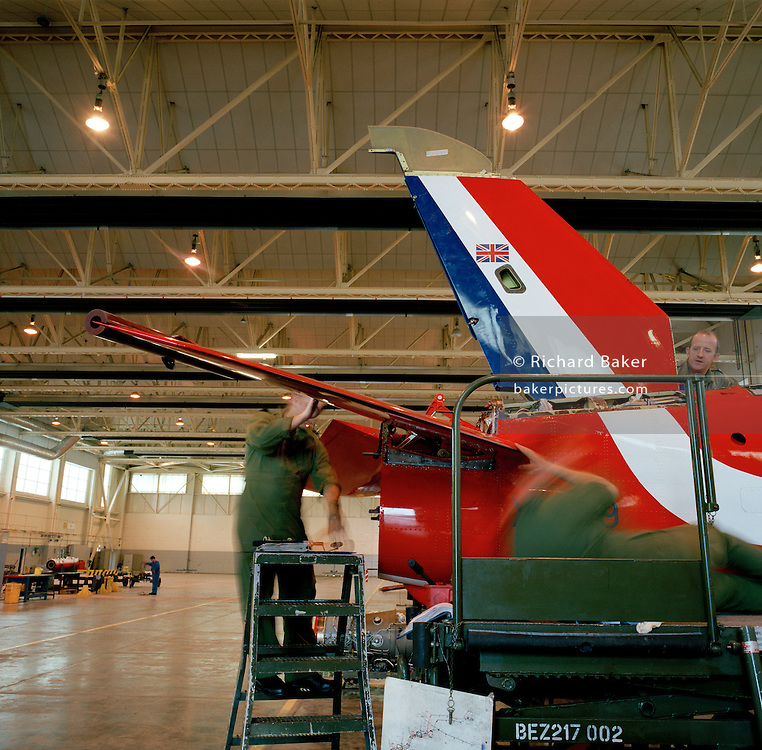 Engineer ground staff perform scheduled maintenance to a Hawk jet in the hangar of the Red Arrows, Britain's RAF aerobatic team.
