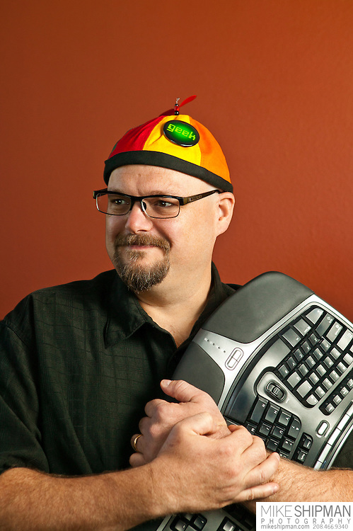 """Portrait of a man wearing a colorful beanie and """"Geek"""" pin, hugging a computer keyboard. MR."""