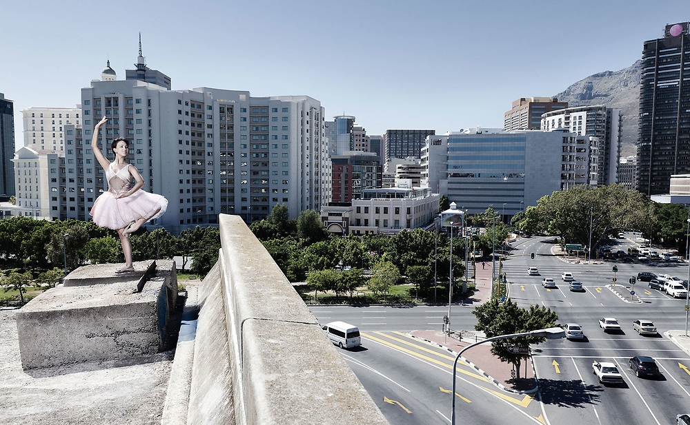 young ballerina dancing on the boarder of a bridge in front of city towers