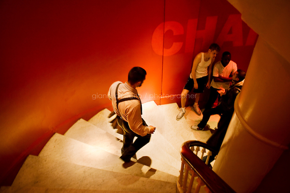 """11 December, 2008. New York, NY. Daniel Alexander Osach (or Dan Alex), 24, walks down the stairs of the David Barton Gym in Chelsea, where he works out almost every day after work. Daniel is a gay Go-Go dancer who grew up in New Haven, CT, and moved to New York a year ago. During the day he works for Christopher Hyland, Inc., a high-end fabrics purveyor. At night, he works as a Go-Go dancer in gay and women clubs around New York City. """"My life is work, gym, dance and sleep"""", Daniela says. Dan has a bachelor in English and majored in Poetry and Economics. After graduation in 2006 he worked as a store manager in a mall for 4 months in Connecticut. Tired and depressed of his job, he went to Florida to relax and then came to New York a year ago. He usually dances at """"The Cock"""", a  East Village gay bar. """"The Cock is not an institution. It's a landmark"""" Daniel says. Daniel aspires to become maybe a teacher or to work for a travel magazine. """"What I would really love to do is to live my life laying down at the beach and reading poetry""""<br /> <br /> ©2008 Gianni Cipriano for The New York Times<br /> cell. +1 646 465 2168 (USA)<br /> cell. +1 328 567 7923 (Italy)<br /> gianni@giannicipriano.com<br /> www.giannicipriano.com"""