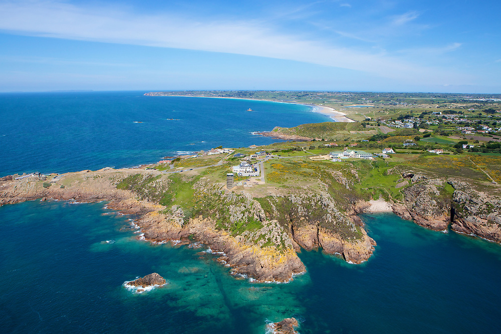 Aerial view of the turquoise clear water surrounding the cliffs and Radio Tower at Corbiere with St Ouen's beach in the distance in Jersey, Channel Islands