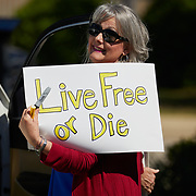 """RALEIGH, NC - APRIL 14: A protestor from a grassroots organization called """"REOPEN NC"""" holds up a sign that reads """"Live Free or Die"""" at a parking lot adjacent to the North Carolina State Legislative building downtown Raleigh, NC on April 14, 2020. Some protestors stayed in their car to honk their horns every 15 minutes while others gathered on the sidewalk, breaking Governor Cooper's social distancing order. The group was demanding the state economy be opened up no later than April 29th.  (Photo by Logan Cyrus for AFP)"""