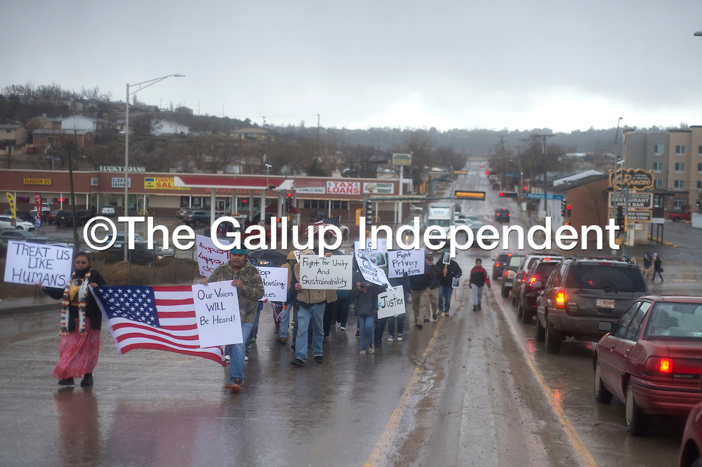 People joining in the Martin Luther King Day march across Miyamura overpass in Gallup Monday carrying signs of civil rights issues and American flags