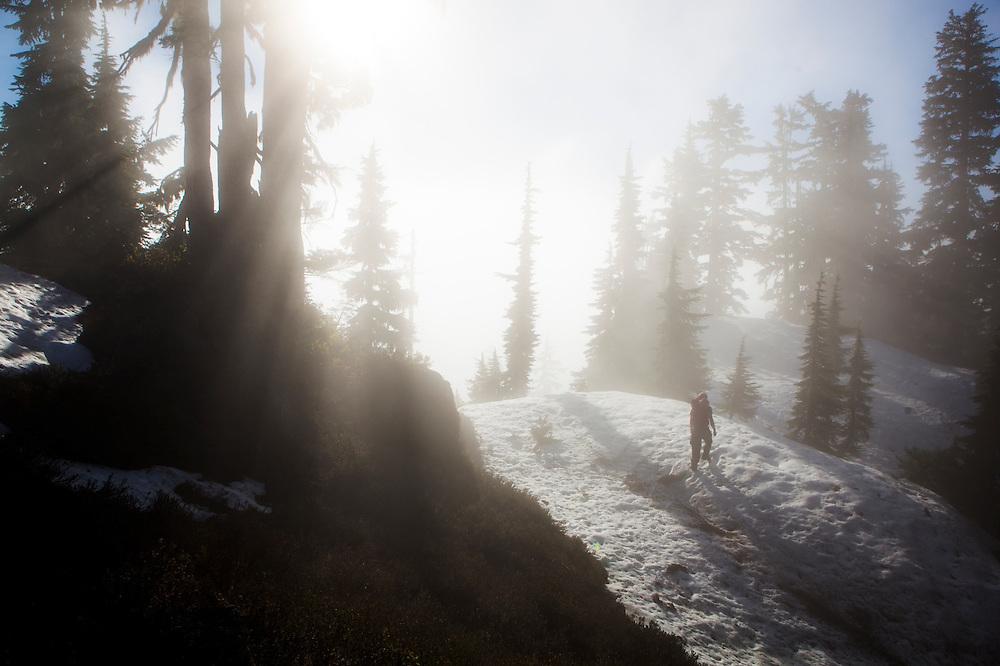 Ian Derrington hikes a ridge shrouded in clouds, North Cascades National Park, Washington.