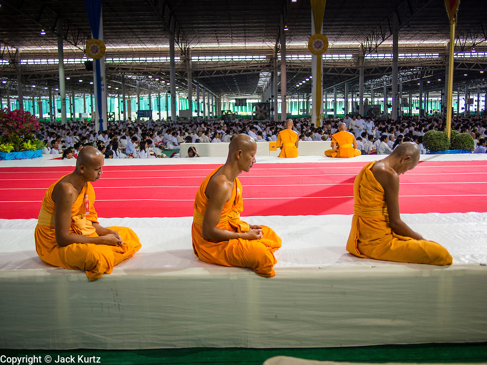 """14 FEBRUARY 2014 - KHLONG LUANG, PATHUM THANI, THAILAND: Buddhist monks meditate during afternoon meditation on Makha Bucha Day at Wat Phra Dhammakaya.  The aims of Makha Bucha Day are: not to commit any kind of sins, do only good and purify one's mind. It is a public holiday in Cambodia, Laos, Myanmar and Thailand. Many people go to the temple to perform merit-making activities on Makha Bucha Day. The day marks four important events in Buddhism, which happened nine months after the Enlightenment of the Buddha in northern India; 1,250 disciples came to see the Buddha that evening without being summoned, all of them were Arhantas, Enlightened Ones, and all were ordained by the Buddha himself. The Buddha gave those Arhantas the principles of Buddhism, called """"The ovadhapatimokha"""". Those principles are:  1) To cease from all evil, 2) To do what is good, 3) To cleanse one's mind. The Buddha delivered an important sermon on that day which laid down the principles of the Buddhist teachings. In Thailand, this teaching has been dubbed the """"Heart of Buddhism."""" Wat Phra Dhammakaya is the center of the Dhammakaya Movement, a Buddhist sect founded in the 1970s and led by Phra Dhammachayo.    PHOTO BY JACK KURTZ"""