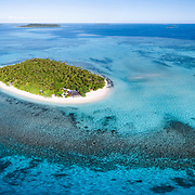 Aerial panorama of Mounu Island Resort in Vava'u, Tonga. This private island getaway is surrounded by coral reef and white sand.