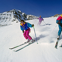 Skiers cruise down Upper Morningstar run at Big Sky resort in Montana.  Lone Mountain is in the background.