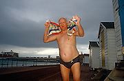 An elderly gentleman towels himself down after emerging from his regular morning swim in the cold waters off Paignton.