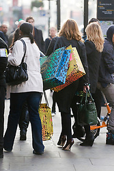 © London News Pictures. 17/11/2011. London, UK. A shopper walks off with bags of shopping following the launch of the new Versace H&M collection at the Regent Street store, London today (17/11/2011). Shoppers had queued for nearly 24 hours to be first in line for Versace's hotly anticipated collection : Ben Cawthra/LNP